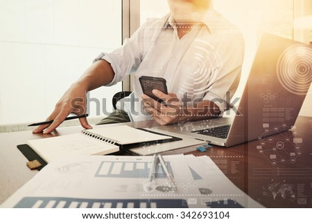 business documents on office table with smart phone and laptop computer and graph business diagram and man working in the background - stock photo