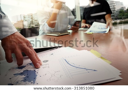 business documents on office table with smart phone and laptop computer and graph business with social network diagram and two colleagues discussing data in the background - stock photo