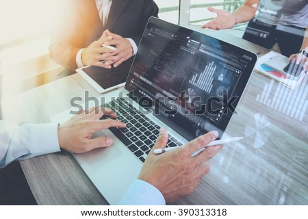 business documents on office table with smart phone and laptop computer and graph financial with social network diagram and three colleagues discussing data in the background
