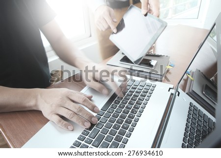 business documents on office table with smart phone and laptop computer and two colleagues discussing data in the background  - stock photo