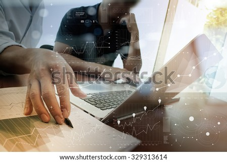 business documents on office table with smart phone and laptop with digital layer effect and two colleagues discussing data in the background - stock photo