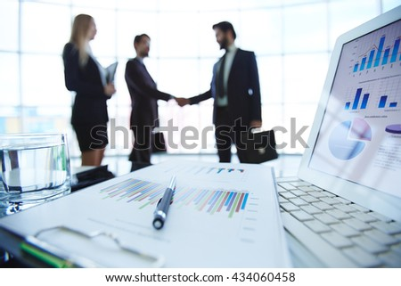 Business documents on workplace with business partners interacting in the background