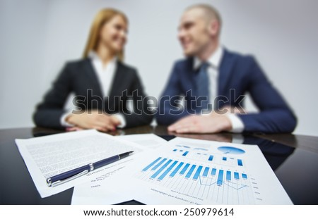Business documents on workplace with two colleagues working on background - stock photo
