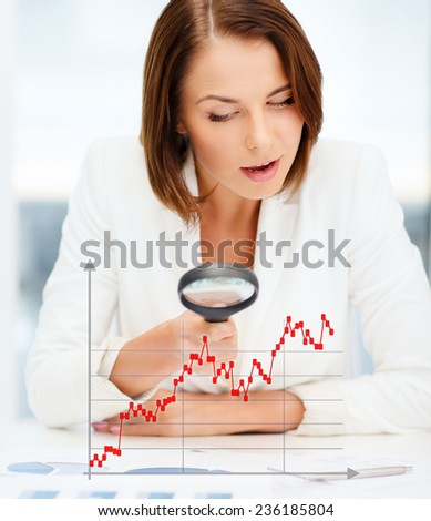 business, documents, statistics and people concept - businesswoman looking through magnifier to graphs in office - stock photo