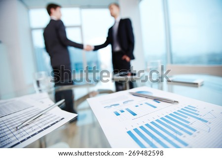 Business documents with economic data and pens on workplace on background of two partners handshaking