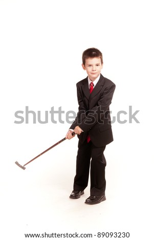 Business dress-code kid with a putter posing in studio on white
