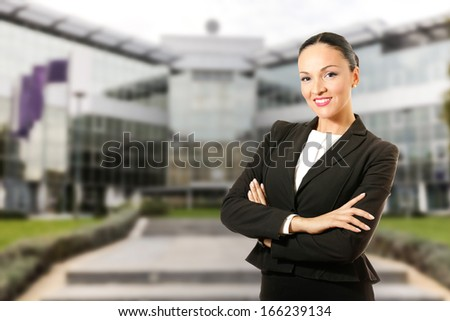 Business dressed woman,standing in front of the bank building.