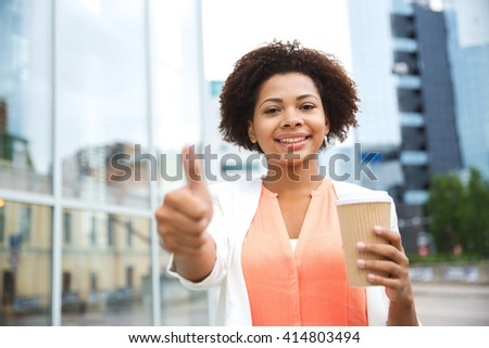 business, drinks, gesture and people concept - young smiling african american businesswoman with coffee cup in city showing thumbs up - stock photo
