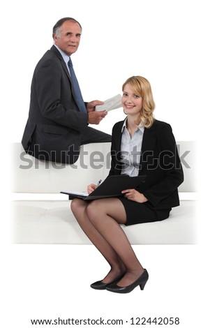 Business duo having meeting on sofa - stock photo