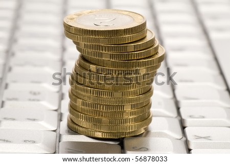 business , e-commerce concept. stack of coins on computer keyboard - stock photo