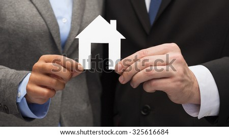 business, eco and real estate concept - businessman and businesswoman holding white paper house