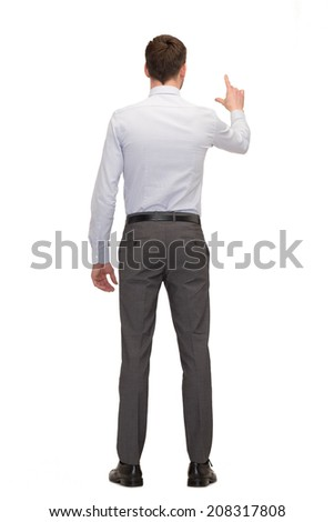 business, education and office concept - businessman or teacher pointing on something from back