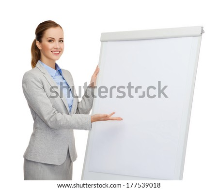 business, education and office concept - smiling businesswoman standing next to flip board and pointing hand - stock photo