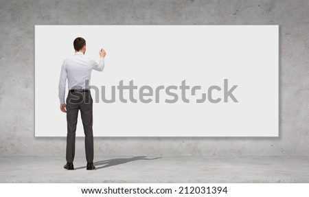 business, education and office people concept - businessman or teacher with marker writing or drawing something on white blank board over concrete wall background from back - stock photo