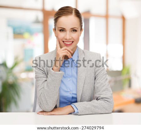 business, education and people concept - smiling businesswoman sitting at table over office background - stock photo