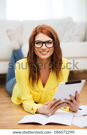 business, education and technology concept - smiling female student in eyeglasses with notebooks and tablet pc computer at home - stock photo