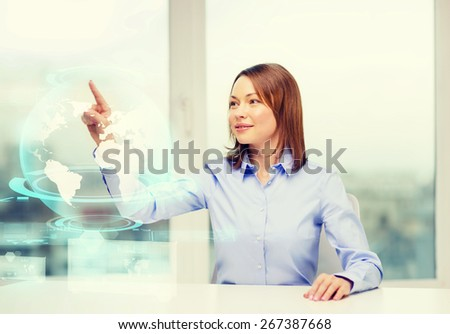 business, education and technology concept - smiling woman pointing to earth hologram - stock photo