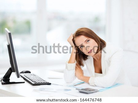 business, education and technology concept - stressed businesswoman with computer, papers and calculator in office