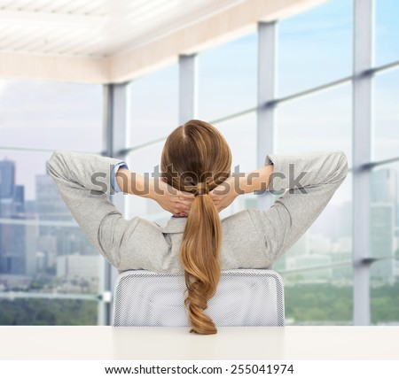 business, education, people and office concept - businesswoman or teacher sitting on chair from back over office window background