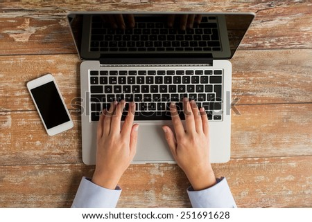business, education, people and technology concept - close up of female hands with laptop computer and smartphone on table - stock photo