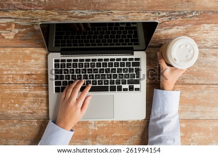 business, education, people and technology concept - close up of female hands with laptop computer and coffee paper cup on table - stock photo