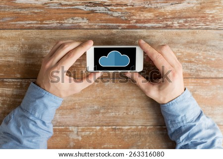business, education, people and technology concept - close up of male hands holding smartphone with cloud computing icon on screen at table - stock photo