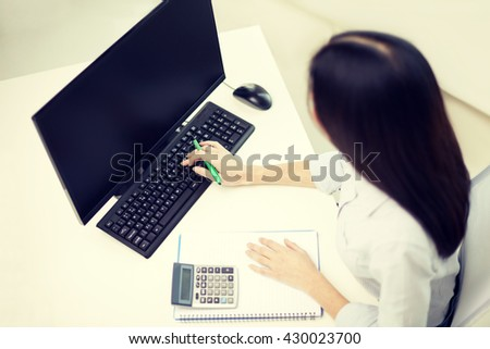 business, education, people and technology concept - close up of woman counting with calculator and writing to notebook at office