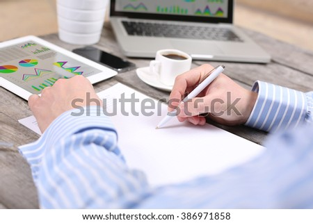 business, education, people and technology concept - male hands with laptop computer, notebook and pen taking notes