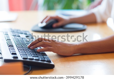 business, education, programming, people and technology concept - close up of african american female hands typing on keyboard and using mouse