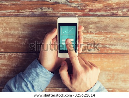 business, education, statistics, people and technology concept - close up of male hands holding smartphone and pointing finger to graph and text on screen at table - stock photo