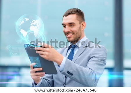 business, education, technology and people concept - smiling businessman working tablet pc computer, virtual screens and globe hologram on city street - stock photo