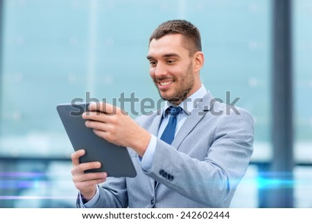 business, education, technology and people concept - smiling businessman working with tablet pc computer on city street - stock photo