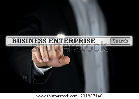 Business enterprise written in a navigation bar on a virtual interface or computer screen with a businessman reaching out his finger to activate the search button from behind. - stock photo