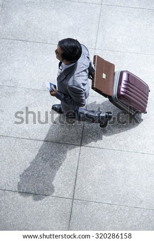 Business executive hurrying to airport, view from the top - stock photo