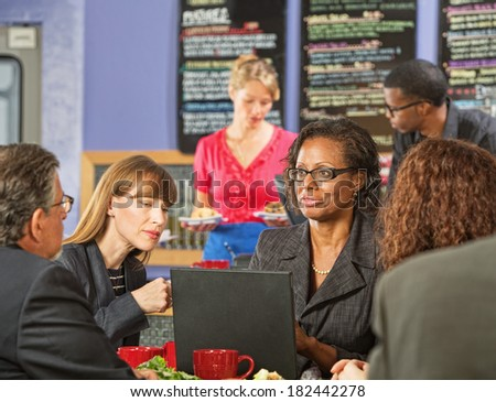Business executive showing coworkers laptop in a coffee house - stock photo