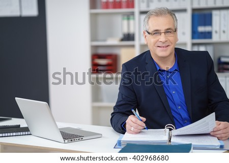 Business executive wearing glasses sitting working at his desk on paperwork in a binder looking at the camera with a smile - stock photo