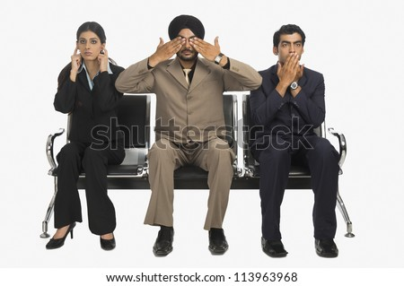 Business executives signing see no evil and speak no evil with hear no evil