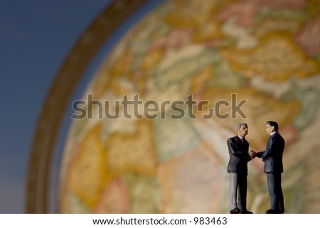 Business figure shaking hands in front of globe with clouds in background - stock photo