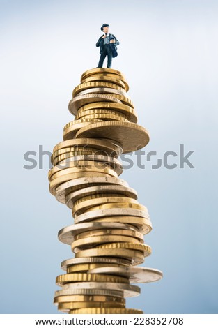 Business figurine on top of invested money - stock photo