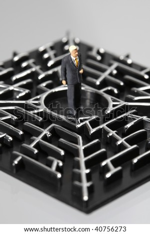 Business figurine standing in the middle of a labyrinth