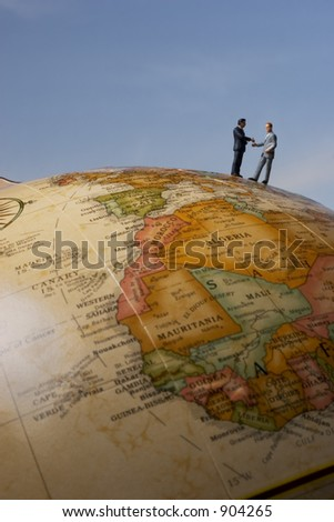 Business figurines on earth globe shaking hands / portrait - stock photo