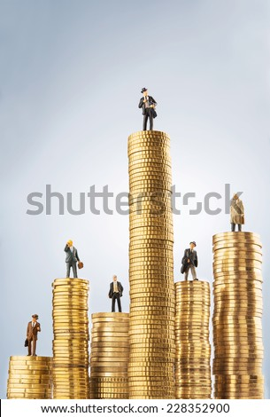 Business figurines on top of invested money - stock photo