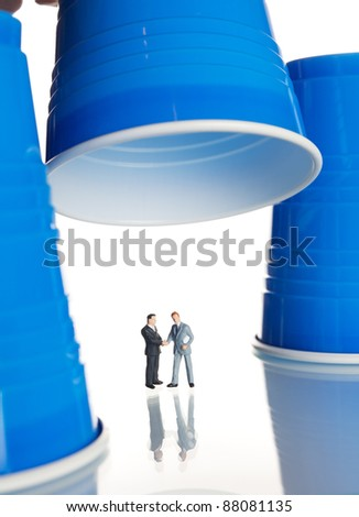 business figurines under plastic coffee cups - stock photo