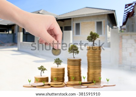 Business Finance and Money concept, Money coin stack growing graph with blurred Construction home  background,Loans to build houses concept - stock photo