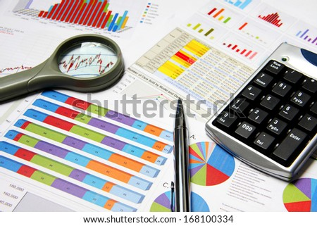 Business finance chart with magnifying glass and silver pen on table.