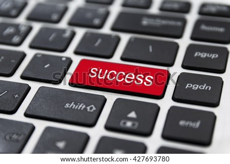 Business finance concept: laptop keyboard with word Success on red enter button, selected focus on enter button