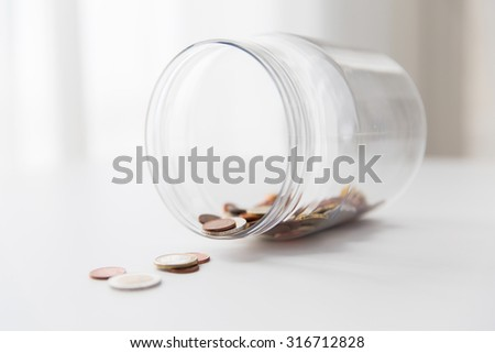 business, finance, investment, money saving and budget concept - close up of euro coins in glass jar on table - stock photo