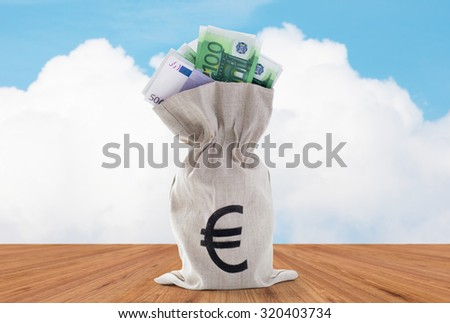 business, finance, investment, saving and cash concept - close up of euro paper money in bank bag over blue sky and wooden floor background - stock photo
