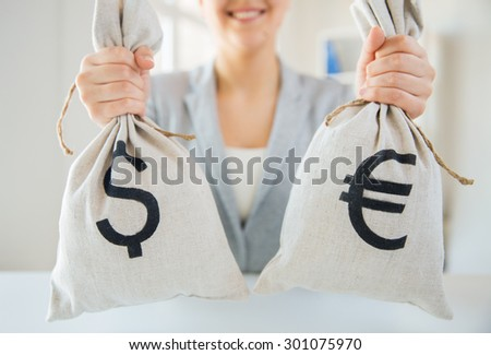 business, finance, saving, banking and people concept - close up of woman hands holding dollar and euro money bags - stock photo