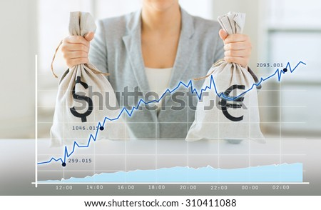 business, finance, saving, banking and people concept - close up of woman hands holding dollar and euro money bags with growing chart - stock photo